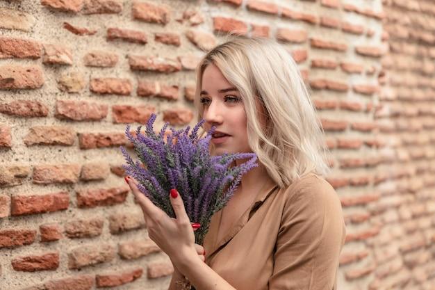 Frau, die beim halten des straußes des lavendels aufwirft