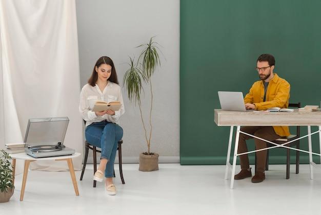 Frau, die beim lesen des buches und des mannes, der am laptop arbeitet entspannt