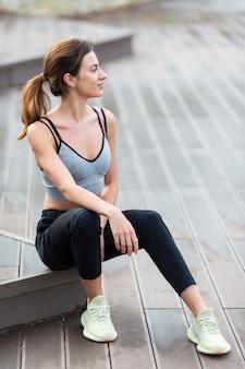 Frau, die beim trainieren im freien ruht
