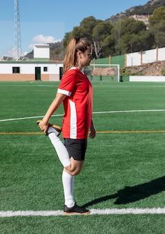 Frau, die bein auf fußballfeld streckt