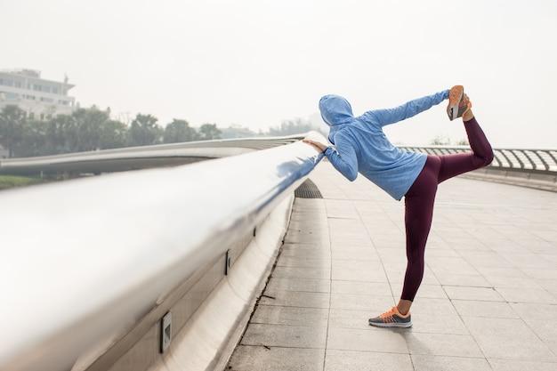 Frau, die bein hält und körper auf brücke ausdehnt