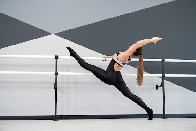 Frau, die beine auf handläufen im tanzstudio ausdehnt