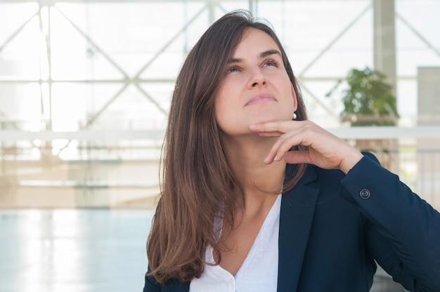 Frau, die beiseite schaut, erwägt und in der hand tablette hält