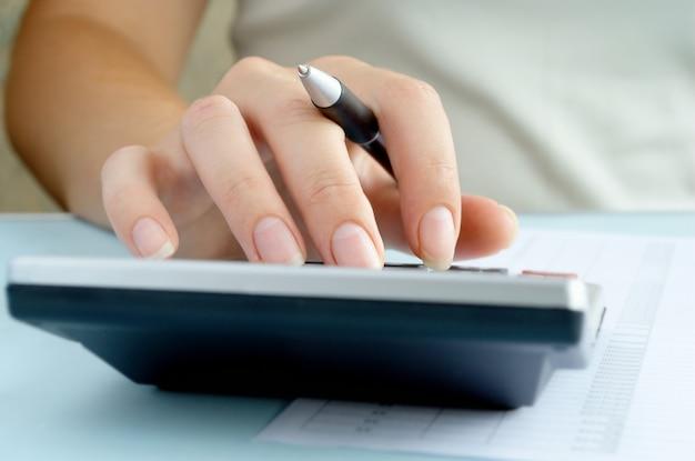 Frau, die berechnungen auf einem taschenrechner tut