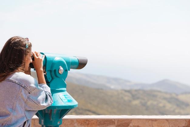 Frau, die berge mit ferngläsern betrachtet