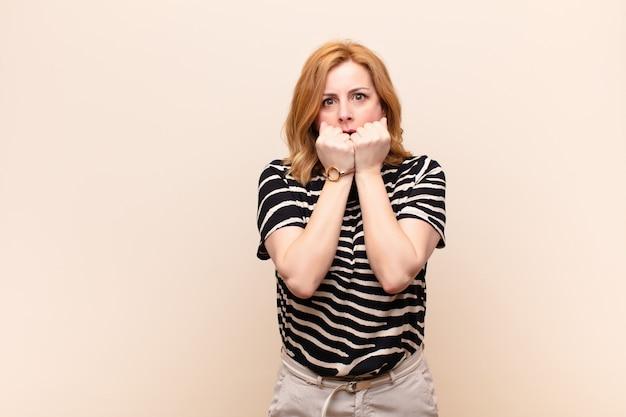 Frau, die besorgt, ängstlich, gestresst und ängstlich aussieht, fingernägel beißt und zum seitlichen kopierraum schaut