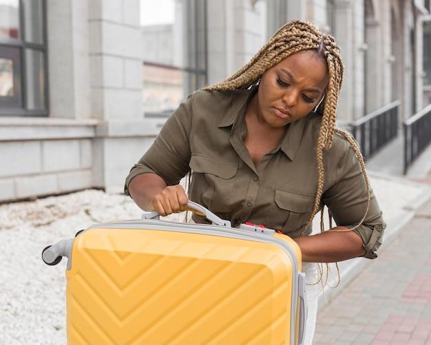 Frau, die besorgt auf ihr gepäck schaut