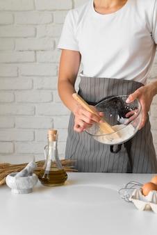 Frau, die bestandteile in schüssel mit holzlöffel mischt