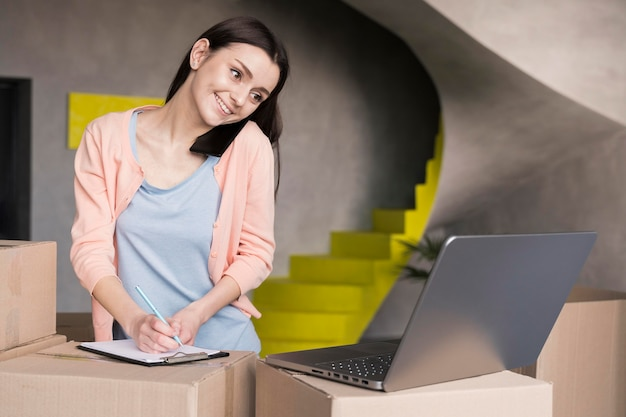 Frau, die bestellungen vom online-shop schreibt, um zu liefern