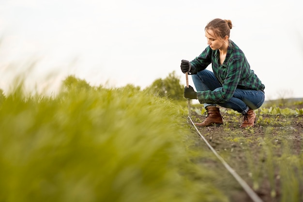 Frau, die bewässerungsschlauch installiert