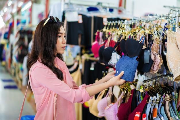 Frau, die bh im einkaufsspeicher wählt und kauft