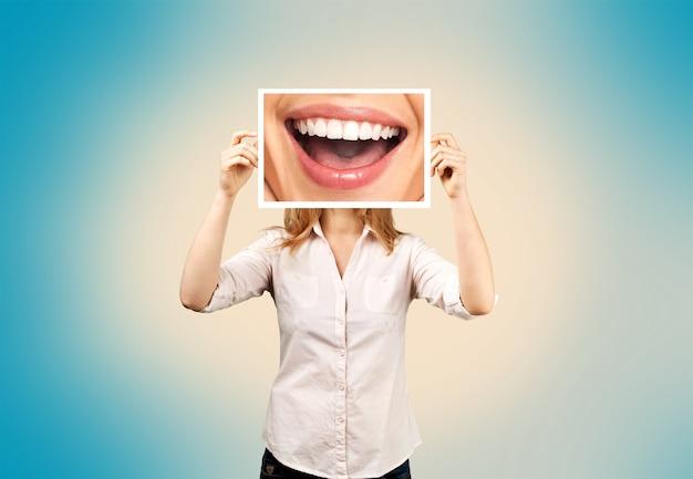 Frau, die bild mit großem lächeln hält. konzeptfoto auf dunklem hintergrund