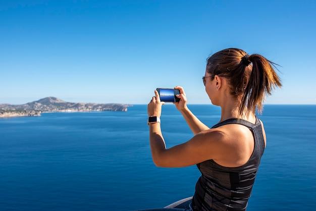 Frau, die bilder mit ihrem smartphone zur landschaft, in der natur vom peñon de ifach in calpe macht