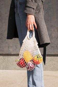 Frau, die bio-gemüse trägt