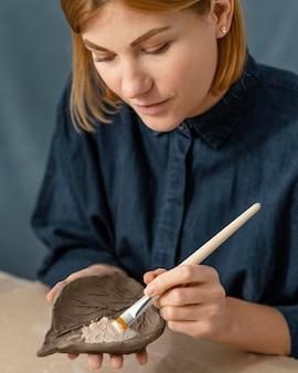 Frau, die blattnahaufnahme malt