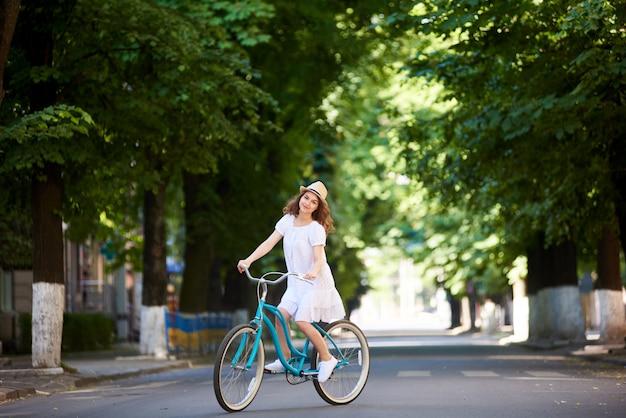 Frau, die blaue fahrradmitte der leeren straße fährt