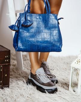 Frau, die blaue klassische tasche hält und graue turnschuhe mit schwarzer sohle trägt
