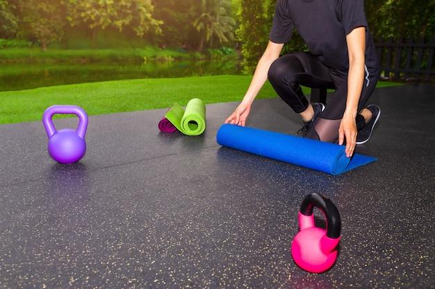 Frau, die blaue yoga- oder eignungsmatte faltet, nach zu hause ausarbeiten. gesundes leben, fit bleiben c