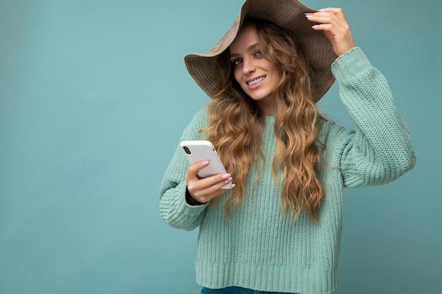 Frau, die blauen pullover und hut trägt, die lokal über blauem hintergrund stehen, der im internet surft