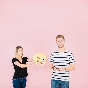 Frau, die blinzelnden emoji ikone nahe lächelndem mann mit handy hält