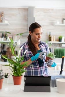 Frau, die blume hält und musik auf tablet-pc hört, während sie in der küche im garten arbeitet