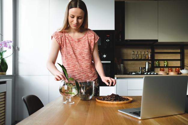 Frau, die blume unter verwendung der online-anweisungen auf dem laptop neu pflanzt