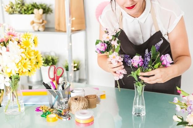 Frau, die blumen in vase auf glasschreibtisch setzt