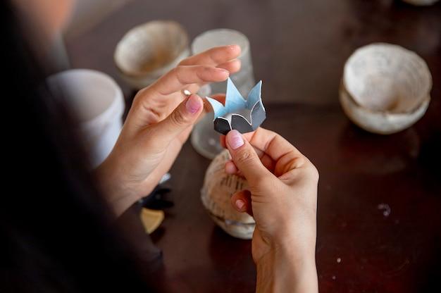 Frau, die blumenorigami aus papier macht