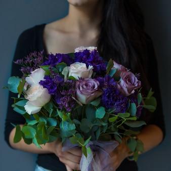 Frau, die blumenstrauß der purpurroten, weißen rosen hält