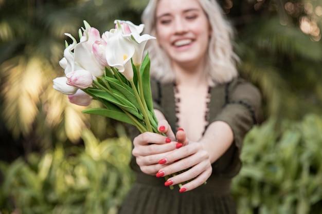 Frau, die blumenstrauß mit tulpen draußen hält