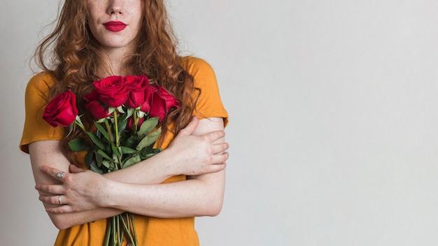 Frau, die blumenstrauß von rosen mit kopienraum hält