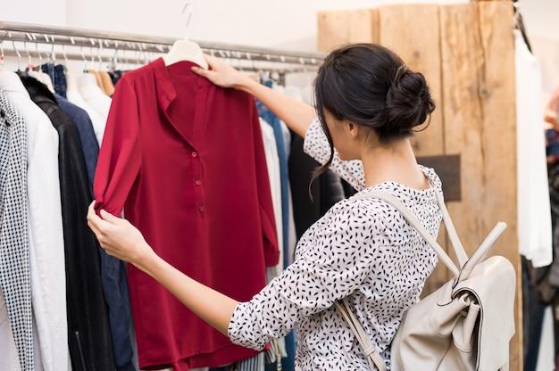 Frau, die bluse von der neuen sammlung von kleidern in einer boutique wählt