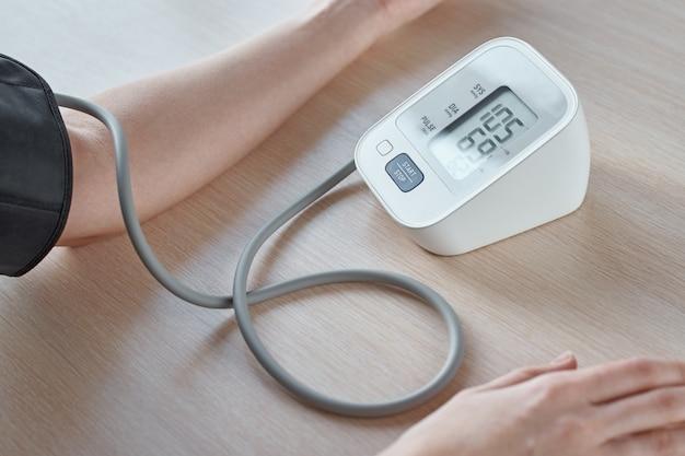 Frau, die blutdruck mit digitalem druckmonitor gegen blauen hintergrund misst. gesundheitswesen und medizinisches konzept