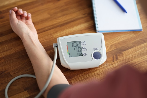 Frau, die blutdruck mit elektronischer tonometer-nahaufnahme misst. diagnose der arteriellen
