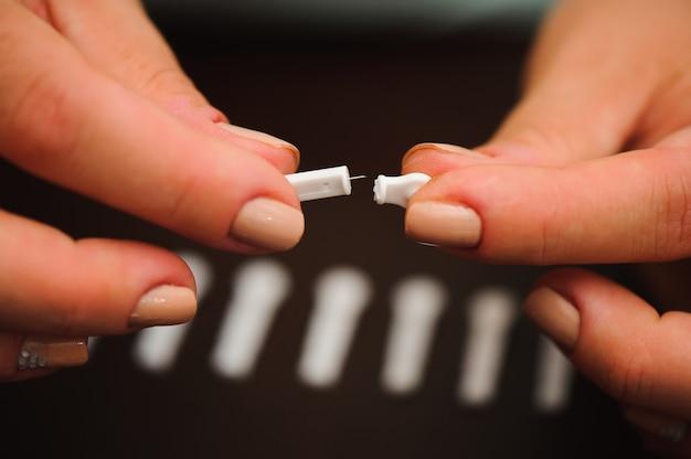 Frau, die blutprobe mit lanzettenstift auf hölzernem hintergrund nimmt. diabetes-konzept.