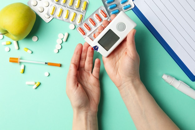 Frau, die blutzuckerspiegel auf tisch mit diabetischem zubehör prüft