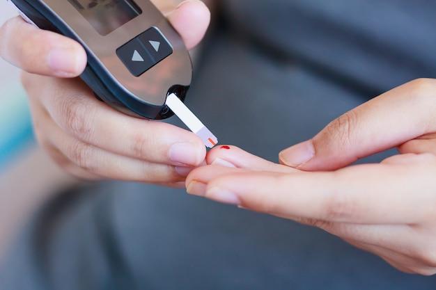 Frau, die blutzuckerspiegel mit glukometer prüft