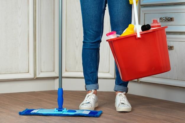Frau, die boden mit mopp in der küche wäscht