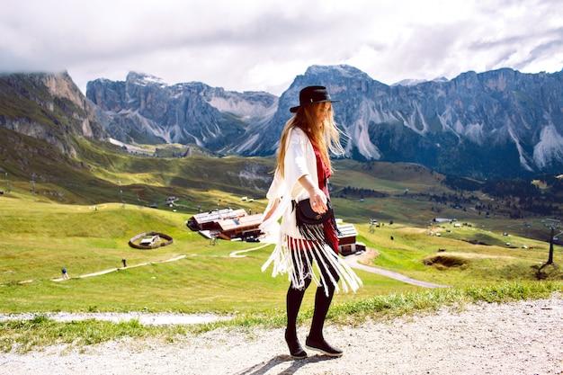Frau, die boho stilvolles outfit trägt, allein geht und atemberaubende aussicht auf österreichische alpenberge genießt