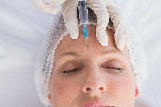 Frau, die botox einspritzung auf ihre stirn empfängt