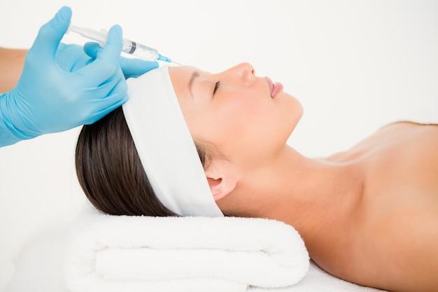 Frau, die botox einspritzung auf ihrer stirn empfängt