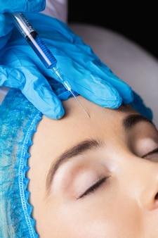 Frau, die botox-injektion auf ihrer stirn erhält