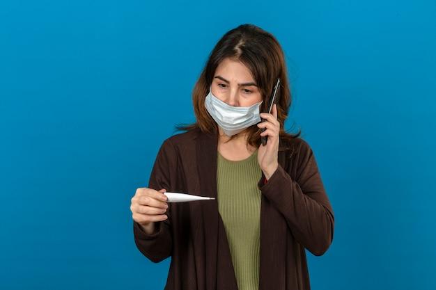 Frau, die braune strickjacke in der medizinischen schutzmaske hält, die smartphone hält, das digitales thermometer in der hand betrachtet, die jemanden anruft, der nervös über isolierte blaue wand schaut