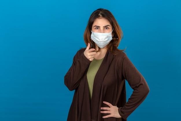 Frau, die braune strickjacke in der medizinischen schutzmaske trägt, die auf die kamera mit ernstem gesicht über isolierter blauer wand zeigt
