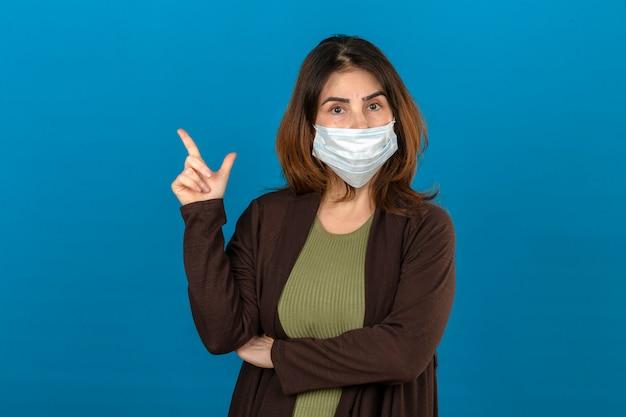 Frau, die braune strickjacke in der medizinischen schutzmaske trägt, die zuversichtlich schaut, zur seite mit dem finger stehend über isolierter blauer wand zeigt