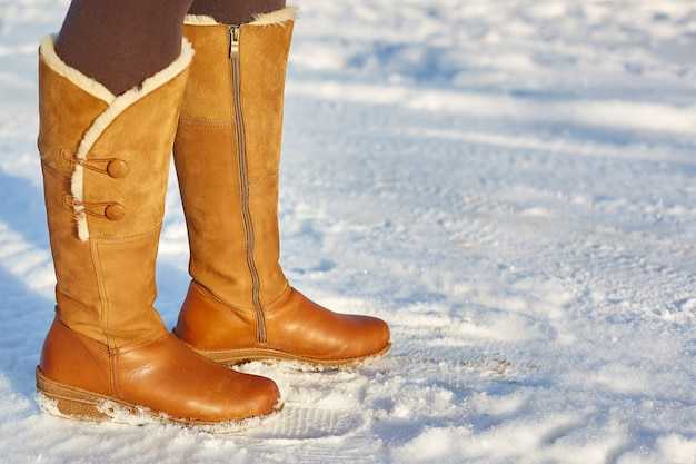Frau, die braune winterstiefel auf dem schnee trägt