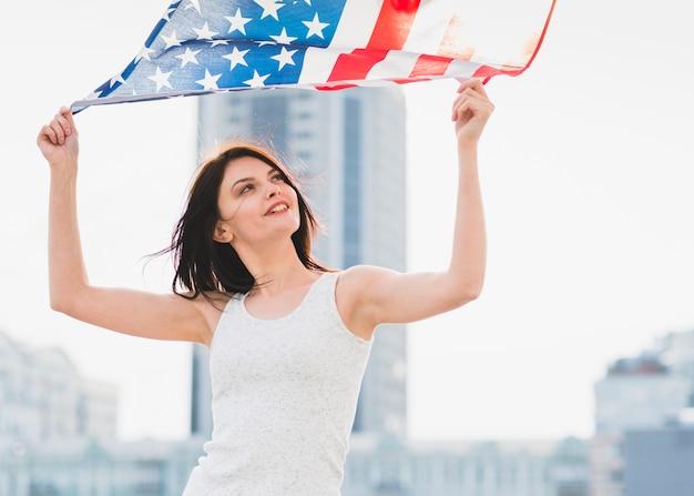 Frau, die breite amerikanische flagge auf hintergrund des geschäftszentrums wellenartig bewegt