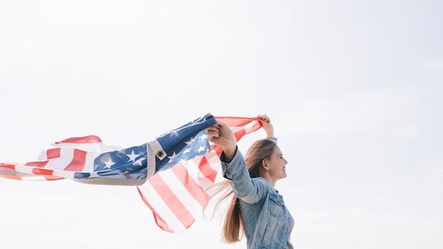 Frau, die breite wellenartig bewegende amerikanische flagge hoch im himmel lächelt und hält