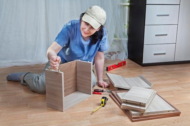 Frau, die brettschubladen zusammenstellt, klebt spanplattenenden verschmiert.
