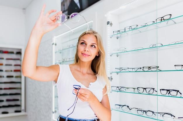 Frau, die brillenrahmen im speicher überprüft